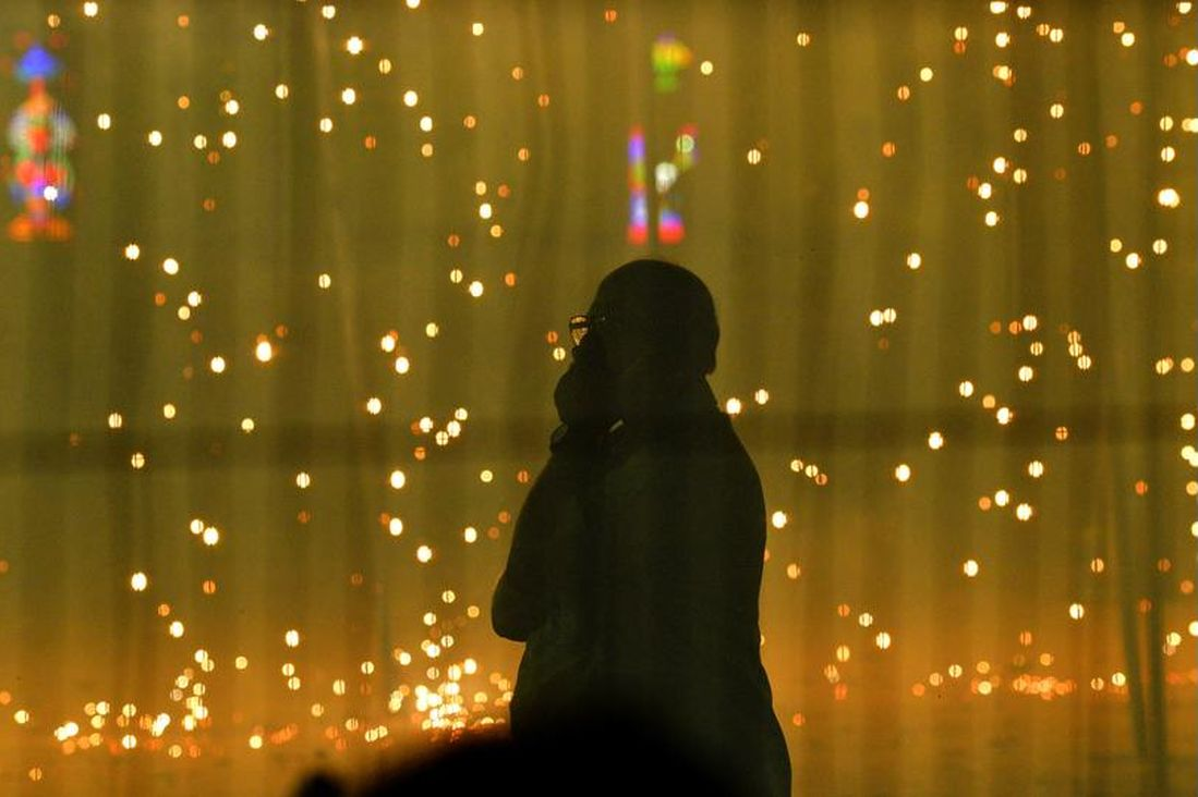 A man watches the fireworks during Dussehra celebration