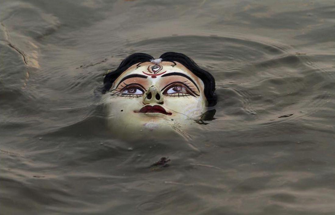 An idol of Hindu goddess Durga floats in water