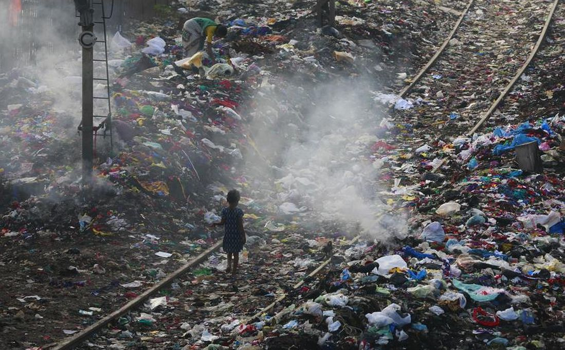 A girl walks on a railway track past piles of dumped garbage in Mumbai