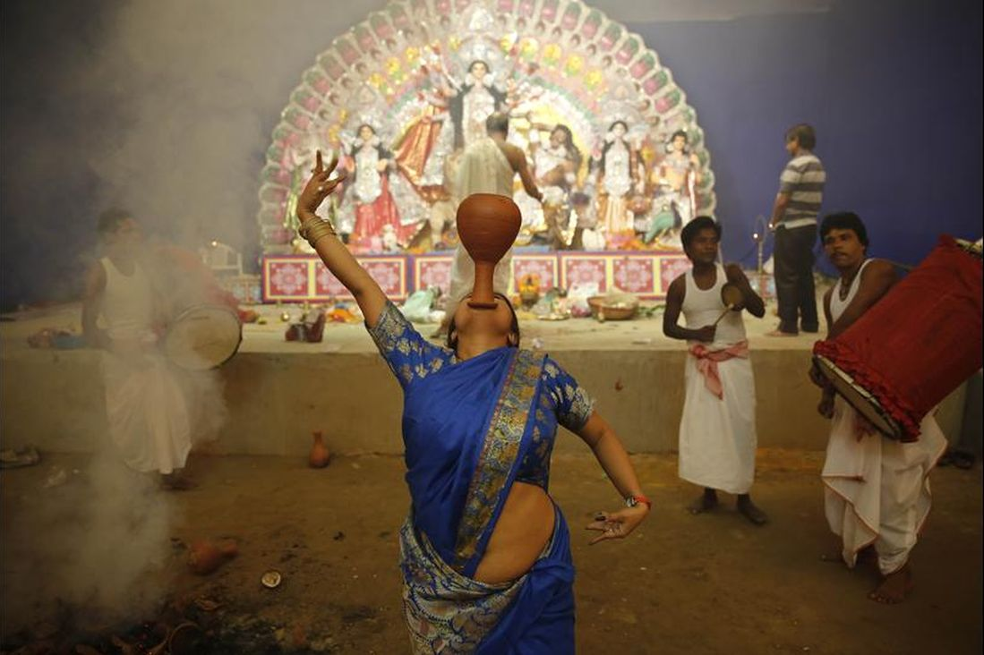 A devotee performs a traditional Dhunuchi dance