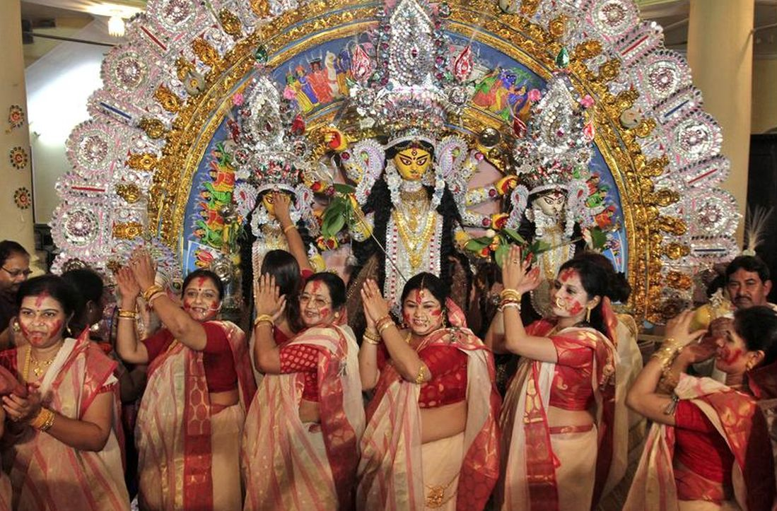 Women perform in front of an idol of goddess Durga