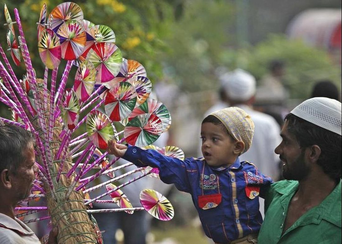 A buys a paper fly-wheel during the celebrations to mark Eid al-Adha