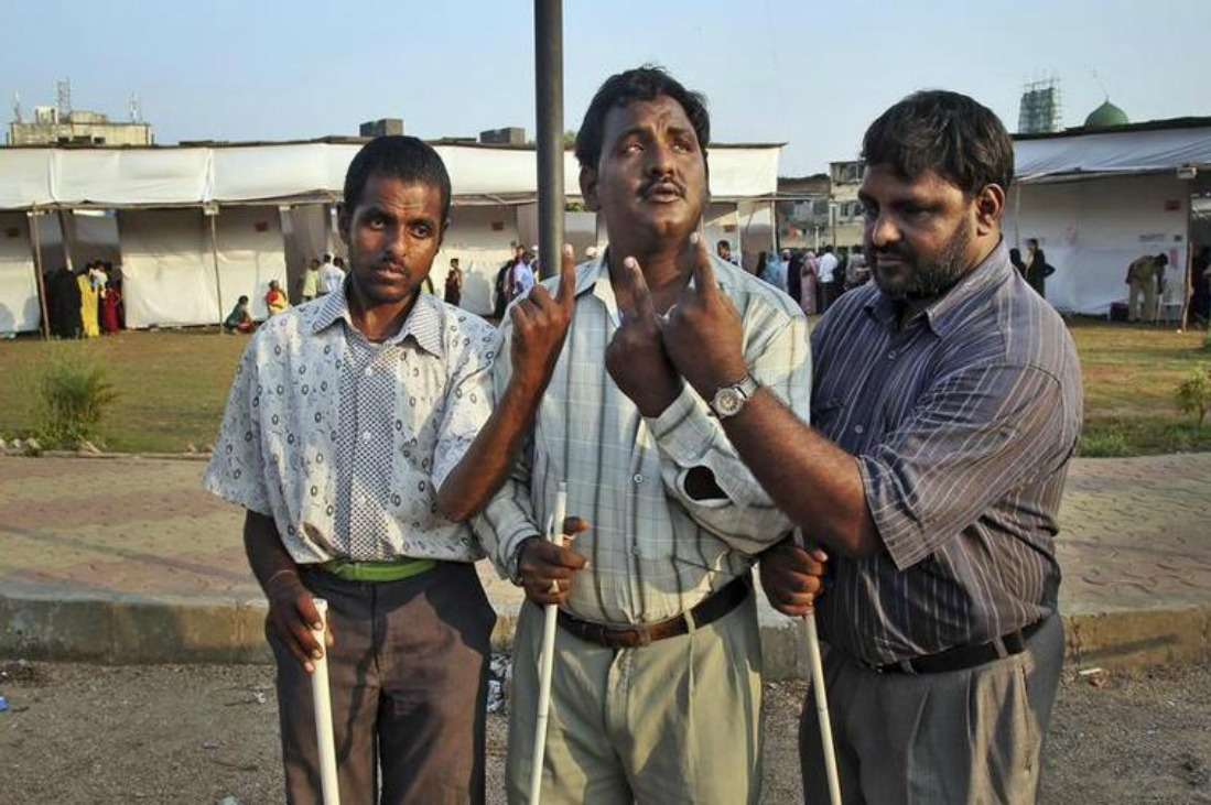 blind men show the ink mark on their index fingers after casting their votes