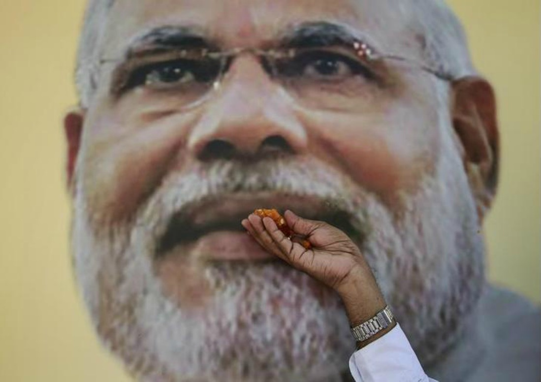 A BJP supporter poses with a Narendra Modi potrait
