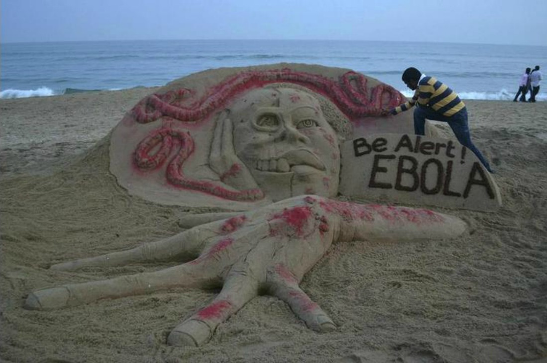 sand artist Sudarshan Pattnaik works on a sand sculpture depicting a message on Ebola