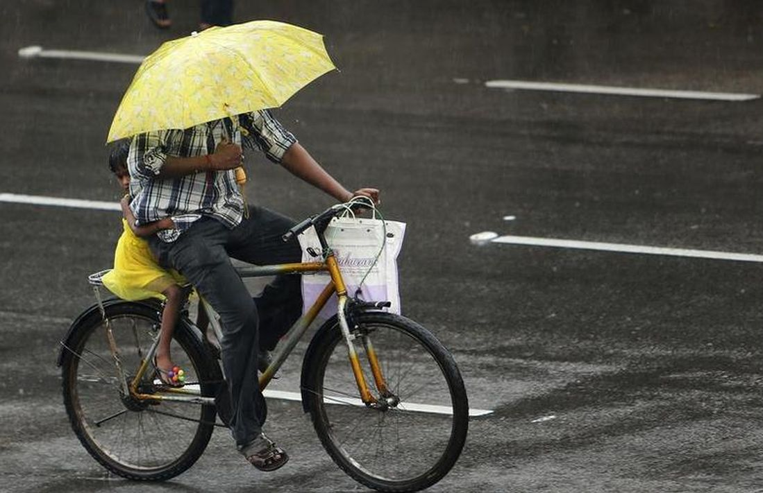A girl clings on to an adult riding a bicycle in the rain