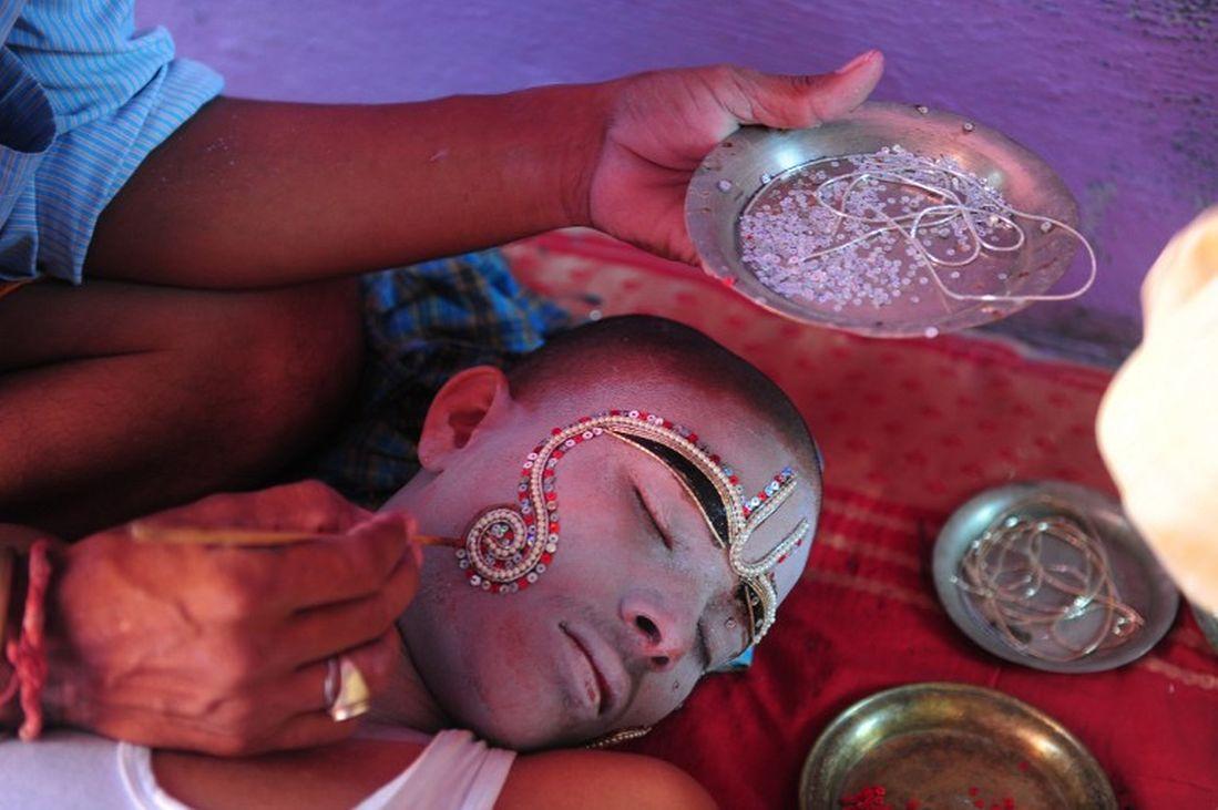 A man applies decorative make-up on a boy depicting Lakshman