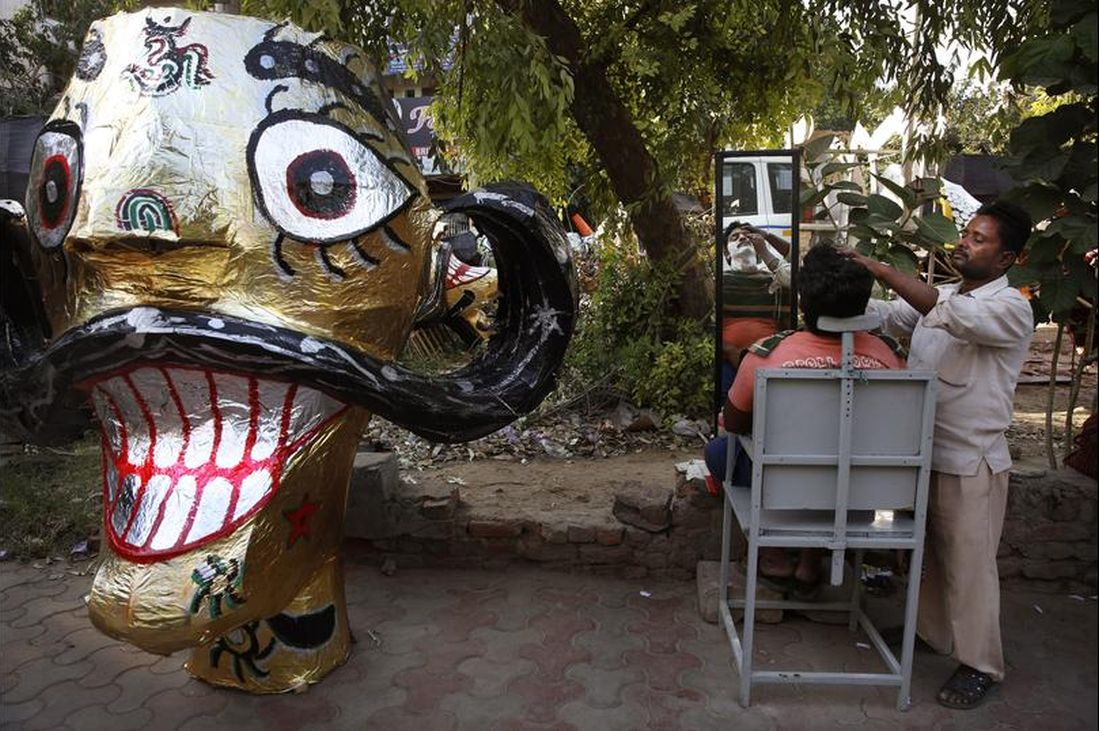 A roadside barber gives a shave to a person next an effigy of Ravana