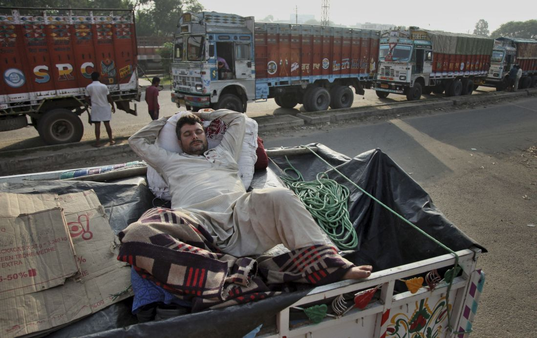 A man sleeps in the back of his truck in Jammu