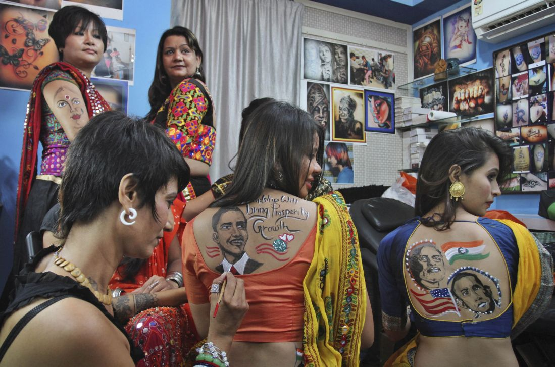 Women get their backs painted with portraits of Barack Obama and Narendra Modi