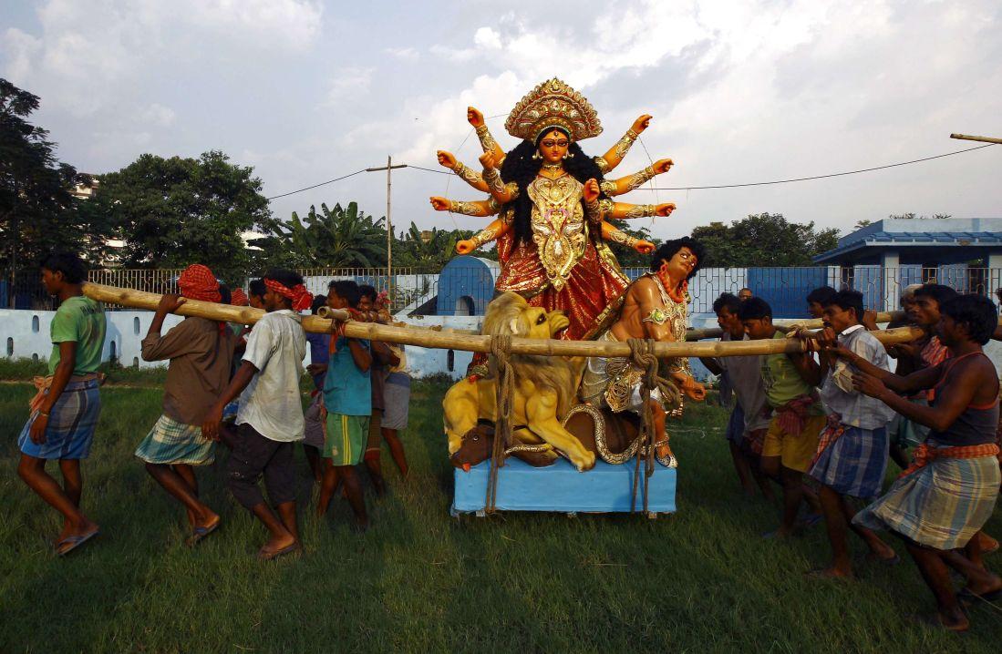 Labourers carry an idol of goddess Durga towards a panda