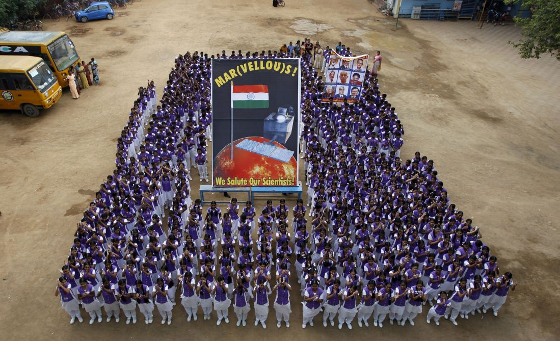 School children pose with a poster of Mars Orbiter Mission satellite