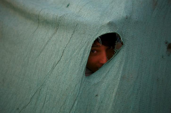 child peeping through tent