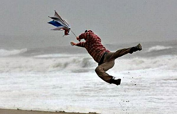 man flying in strong storm