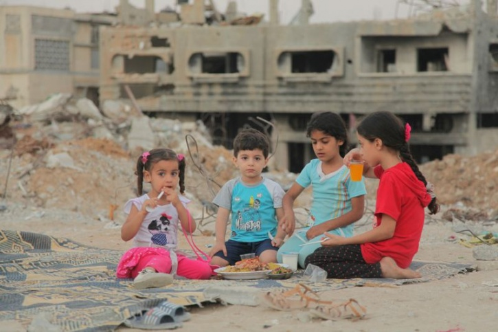 Children Eating in front of the rubble of their homes