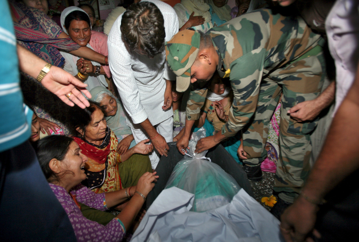 An Indian army soldier opens the body bag containing the body of his colleague Sat Pal Bhasin.