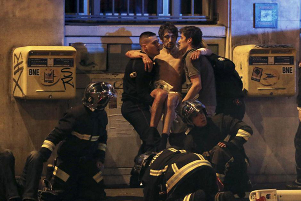 A survivor being helped by securitymen outside Bataclan concert hall
