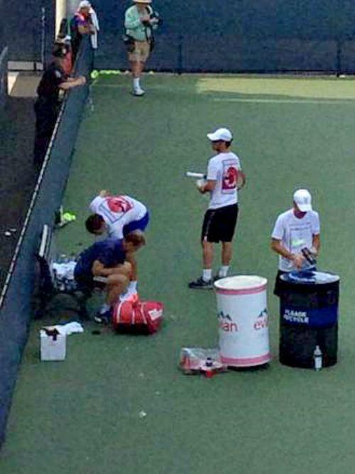 Roger Federer cleans court after practice session