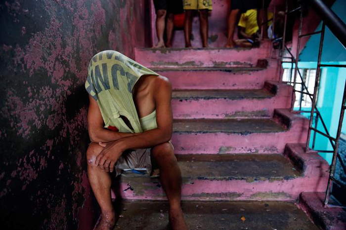 An inmate covers his head as he passes the time inside Quezon City Jail in Manila