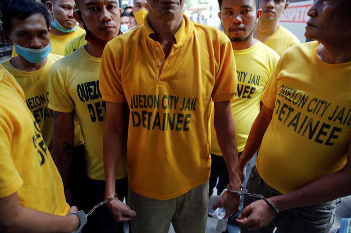 Inmates are handcuffed to each other as they are brought back from hearings to Quezon City Jail in Manila, Philippines