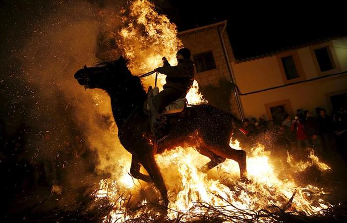 A man rides a horse through the flames