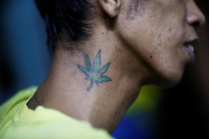 A tattoo is seen on the neck of an inmate in an underground cell