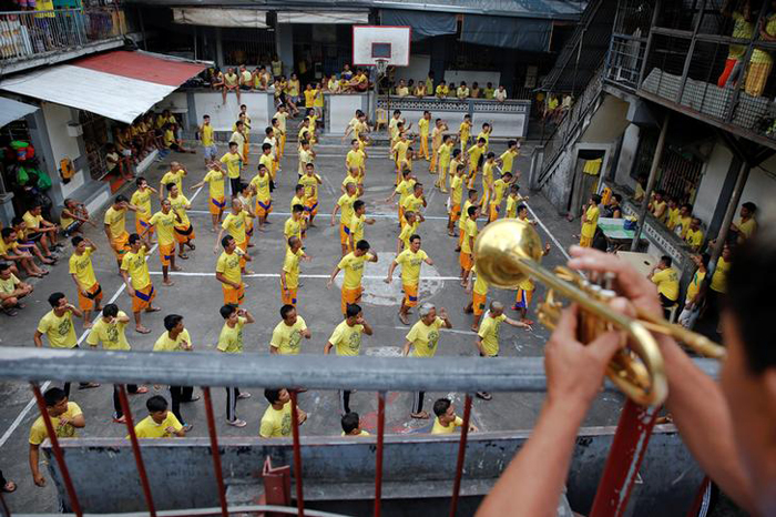 Inmates dance during routine morning exercise at the court inside