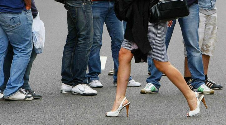 woman walking among men
