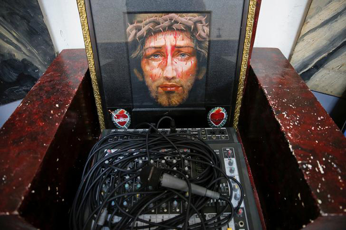 A religious picture is placed next to a microphone and sound system at the chapel of Quezon