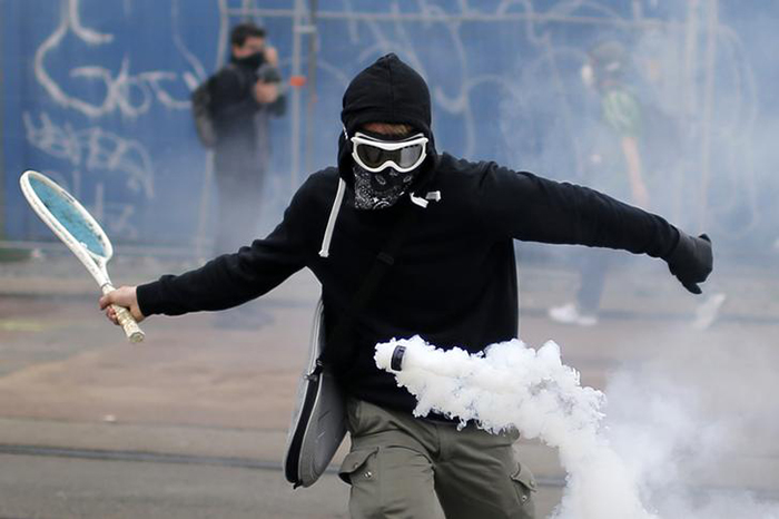 protestor uses a tennis racket