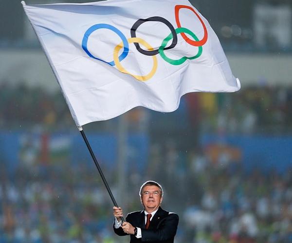 IOC boss Thomas Bach hoisting the Olympics flag