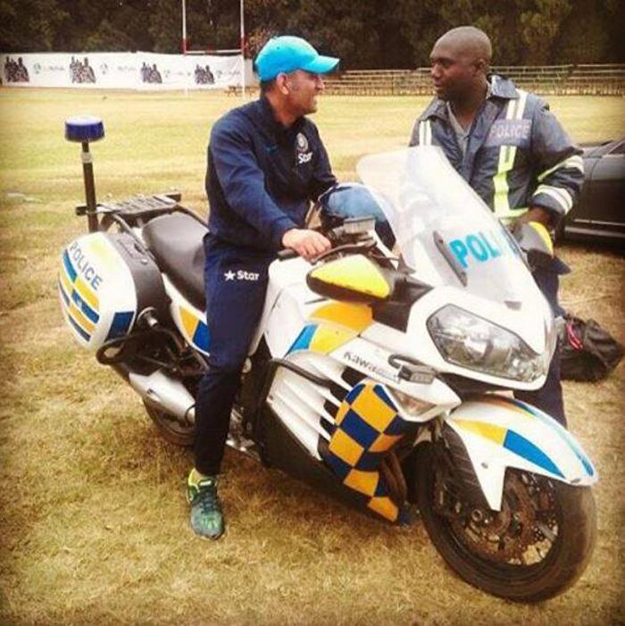 Dhoni rides a bike in Zimbabwe