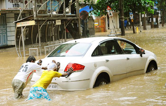 People Push Car in Flood