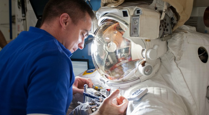 NASA astronaut Chris Cassidy checks on EMUs aboard the space station