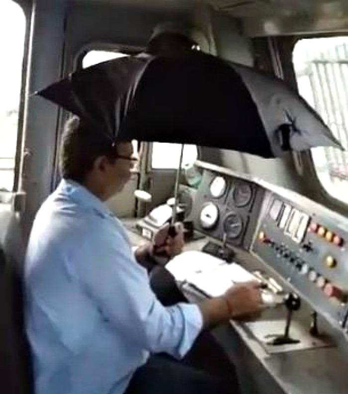 driver holding an umbrella while driving a train