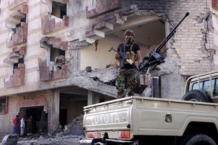 A police trooper mans a machine gun mounted on a patrol truck