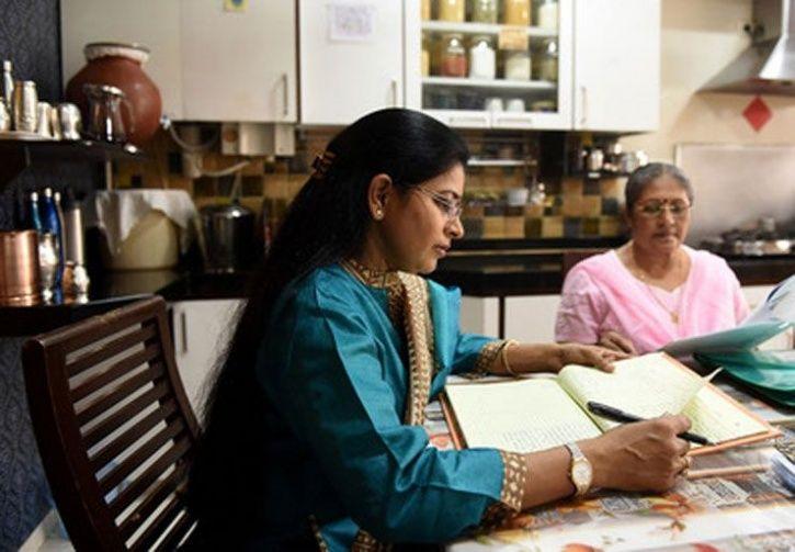 Rashmi and Leelavathi check the customer feedback register