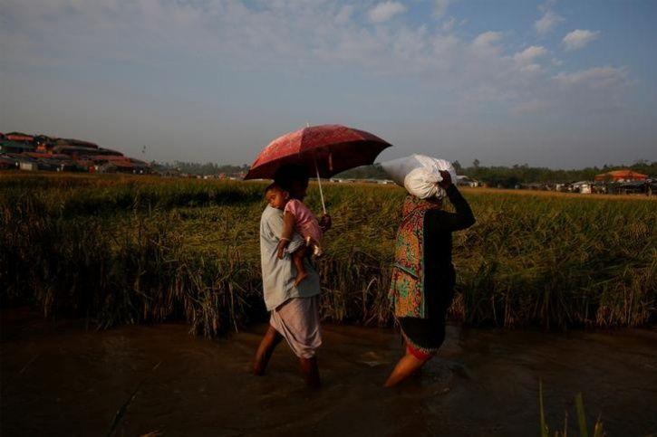 Rohingya refugees wade through water
