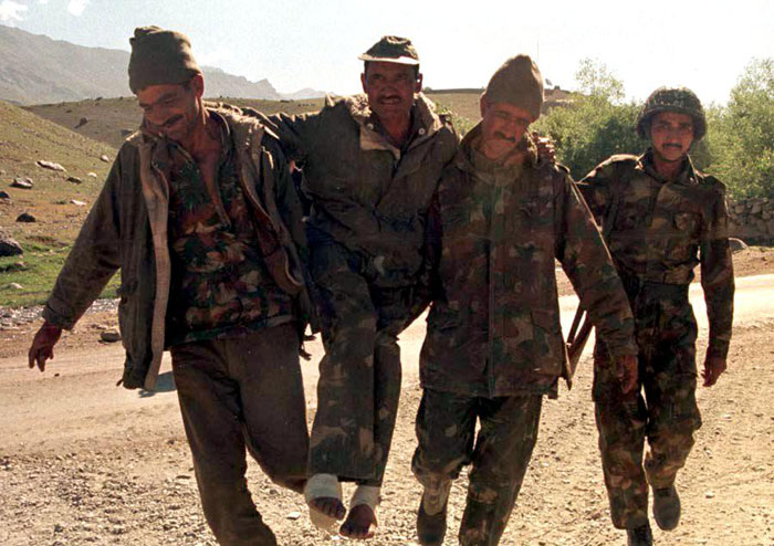 Indian soldIers carry an injured colleague after a fierce gun battle with Moslem infiltrators in the mountains of the Drass sector of Kashmir