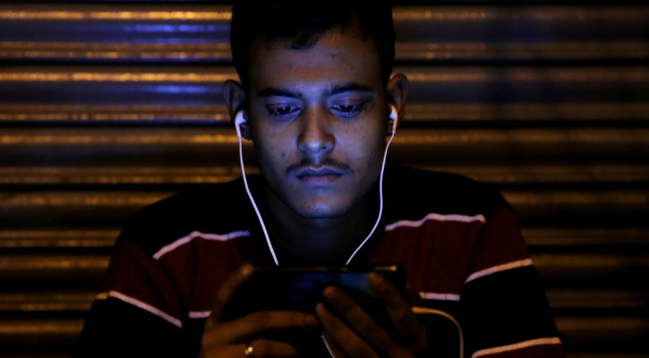 indian man watching a video on his smartphone