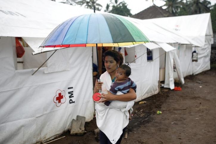 A woman carries a baby at a camp for people who have been evacuated from villages