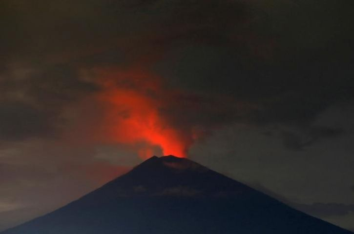 Lava inside the crater of Mount Agung volcano reflects off ash and clouds