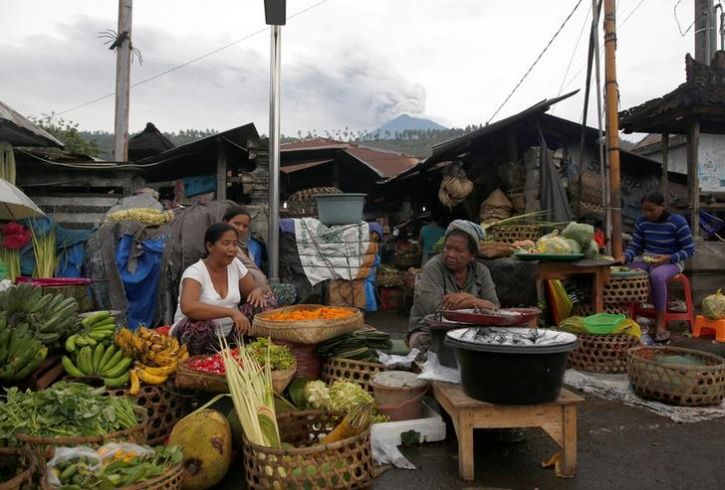 Mount Agung volcano erupts behind as women as the sell food in the morning market in Culik
