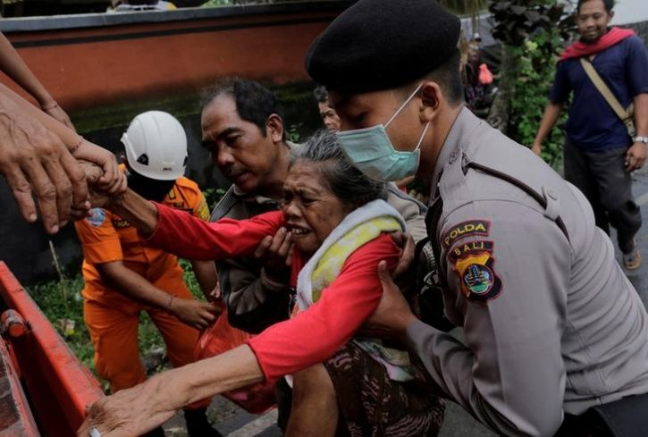 Police evacuate a villager from inside the exclusion zone due to the eruption of Mount Agung volcano