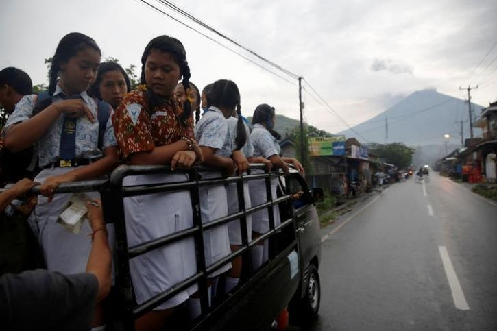 Students ride in a truck to school as Mount Agung volcano erupts near Culik