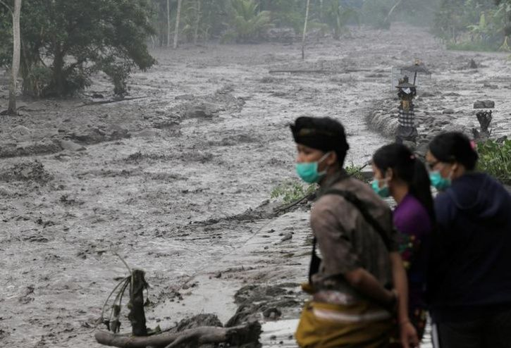 Villagers watch a river overflowing with water mixed with volcanic ash during the eruption of Mount