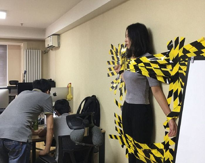 woman taped to a wall