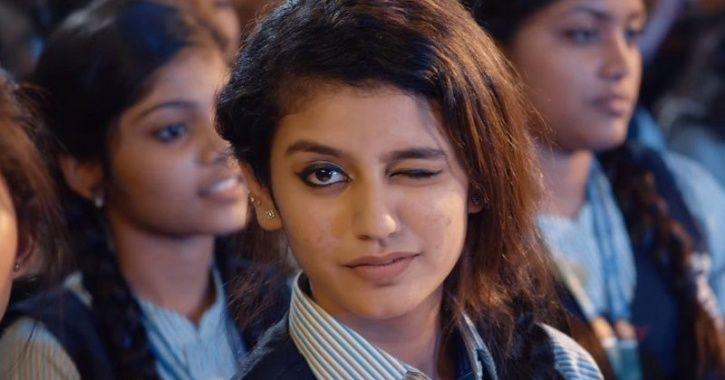 A still of Priya Varrier winking in a song.