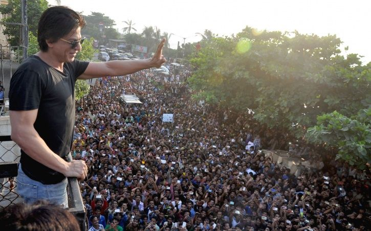A picture of Shah Rukh Khan waving at his fans outside Mannat.