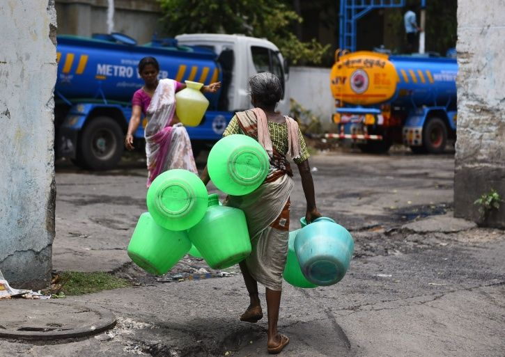 People filling water from a tanker in the situation of crisis.